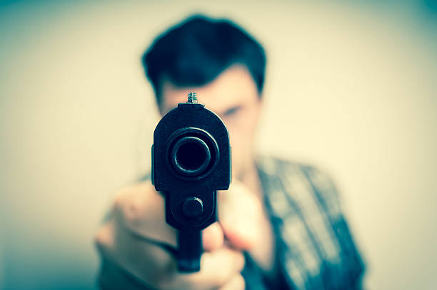 crazy young man aiming gun at you - killer stock photos and pictures