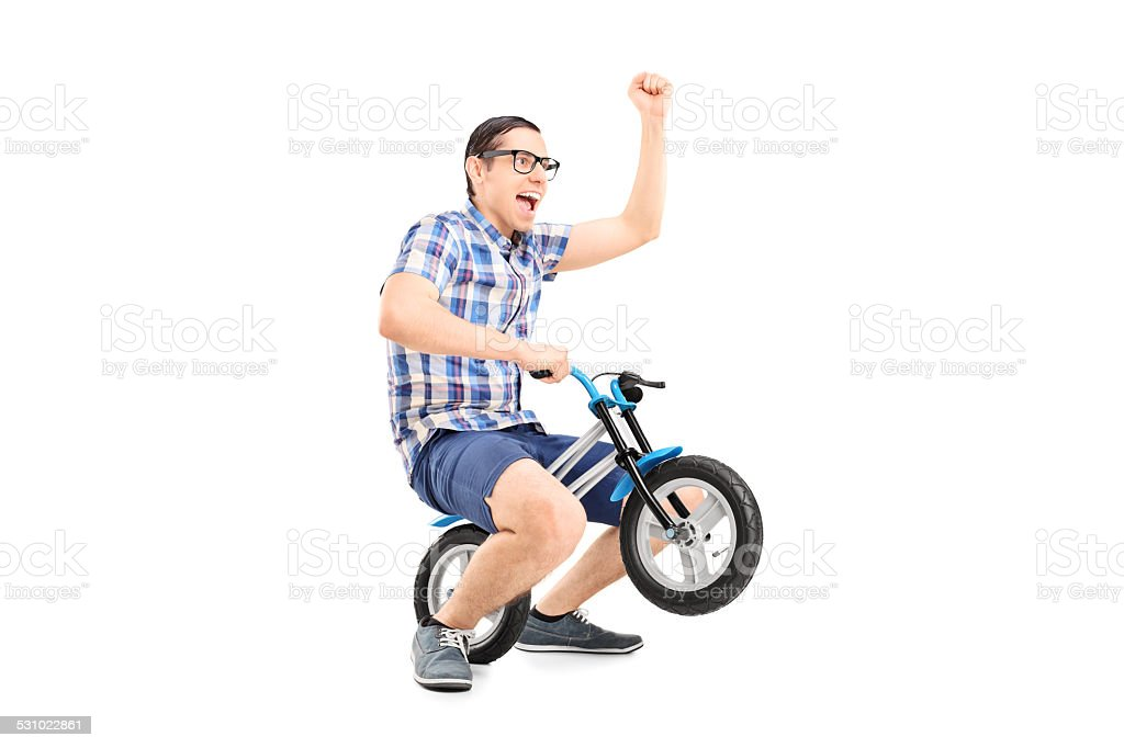 Crazy young man riding a small bike stock photo