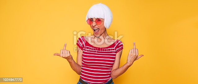 483075616 istock photo Crazy young woman in blonde wig and pink sunglasses having fun 1024947770