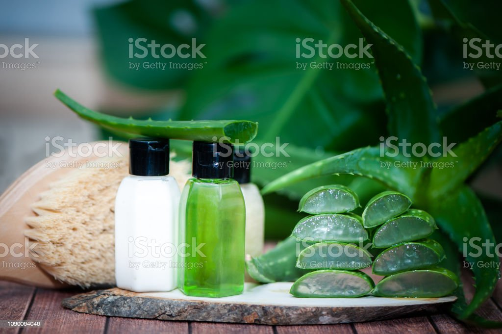 Cream and aloe gel, massage brush juicy scarlet cut into pieces on a natural wooden background . Organic bio anticellulite cosmetics - foto stock