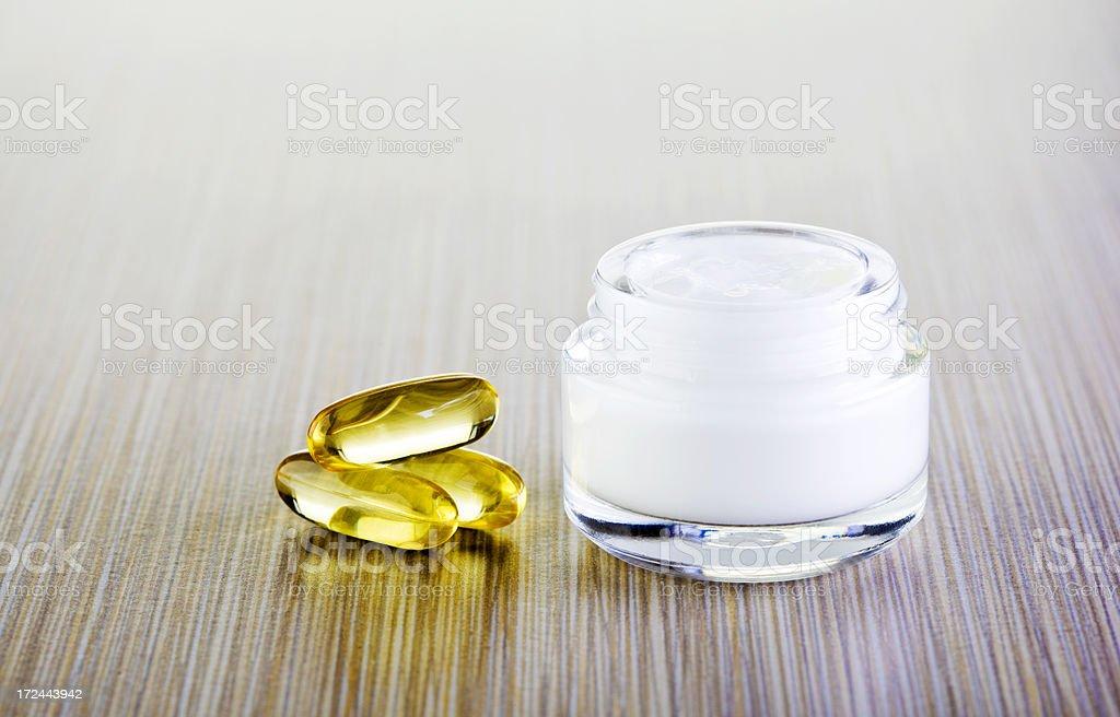 Cream and vitamin pills stock photo