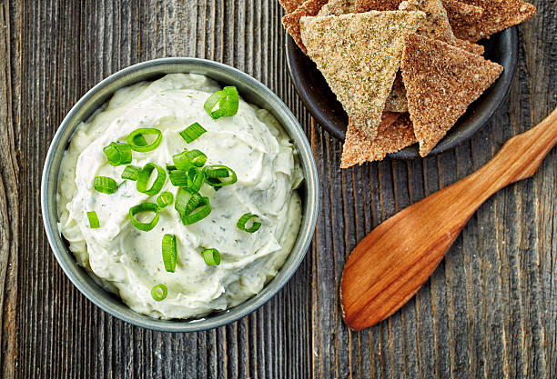 cream cheese with green onions and herbs stock photo