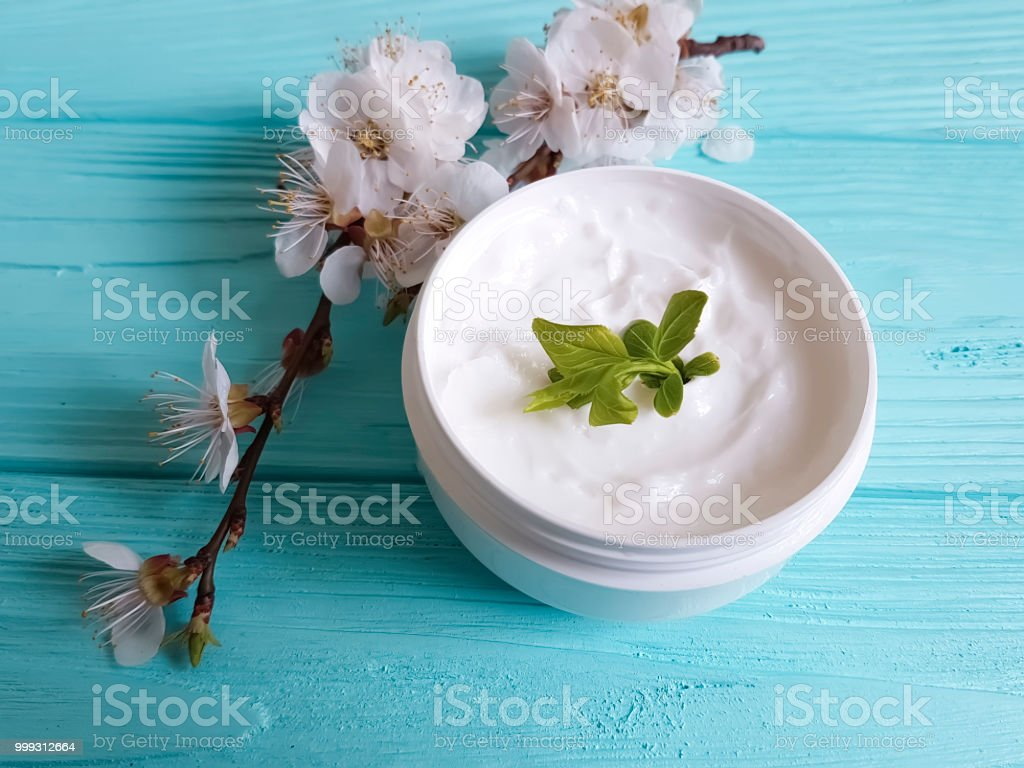 cream cosmetic blossoming cherry on a blue wooden background