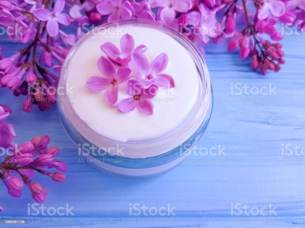 cream cosmetic, flower lilac on blue wooden background