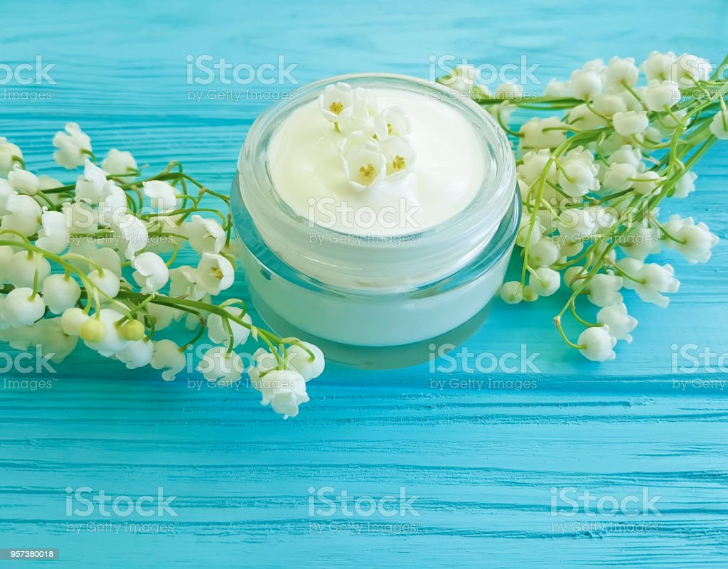 cream cosmetic flower lily of the valley on blue wooden background