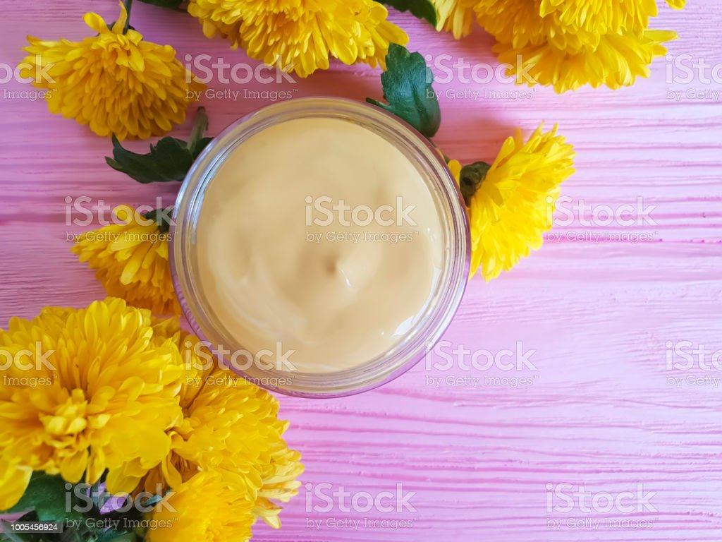 cream cosmetic flowers chrysanthemum yellow on a pink wooden...