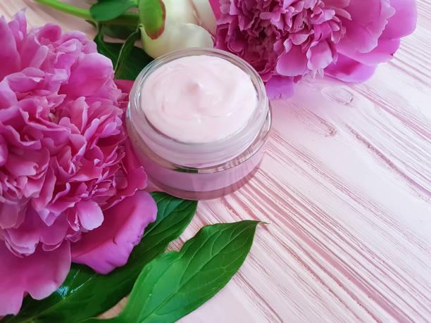 creme kosmetik, pfingstrose blume auf einem rosa hintergrund aus holz - pfingstrosen pflege stock-fotos und bilder