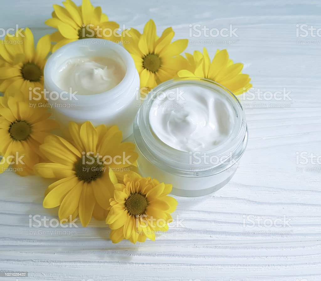 cream cosmetic yellow daisy flowers on a white wooden background