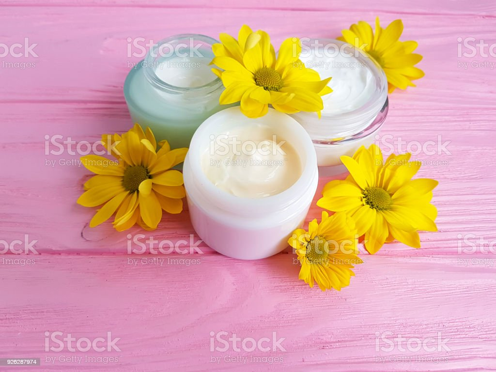 cream cosmetic yellow flowers pink wood background