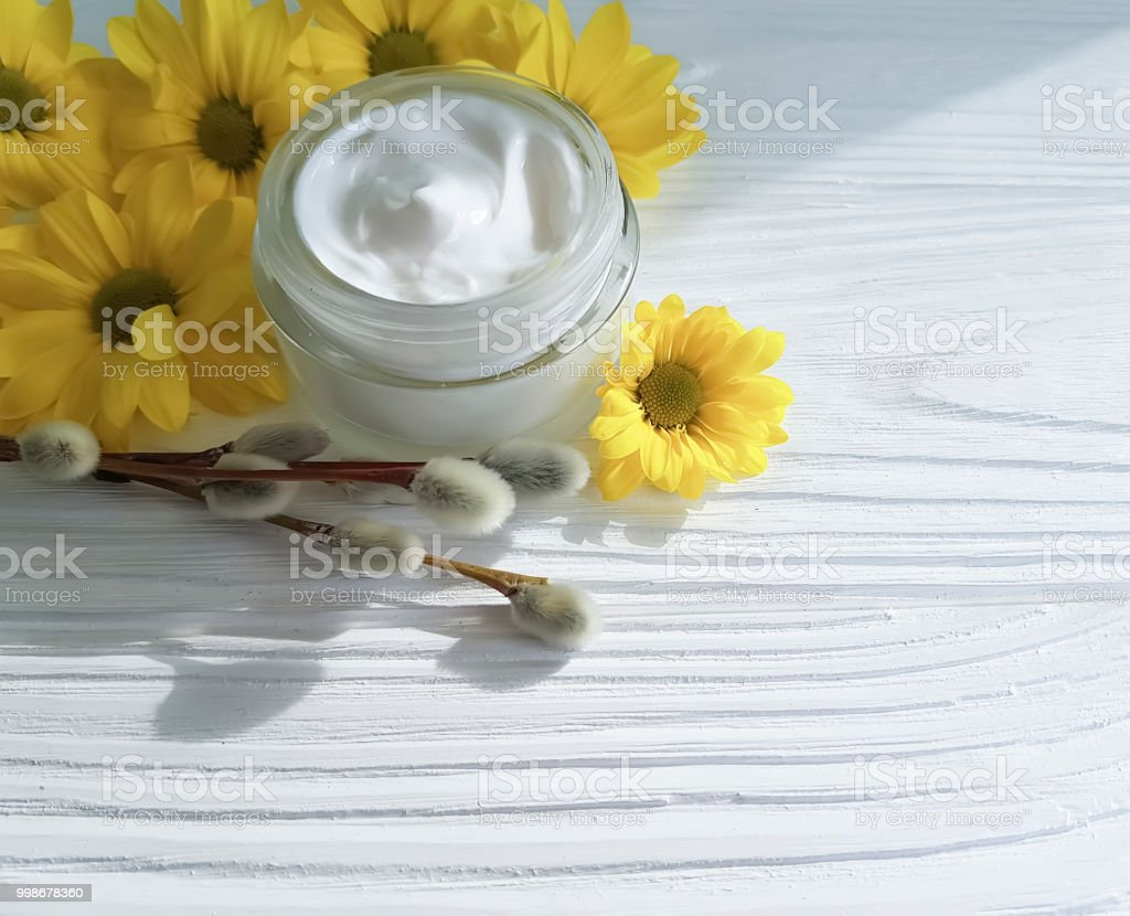 cream cosmetic yellow flowers, willow on a wooden background