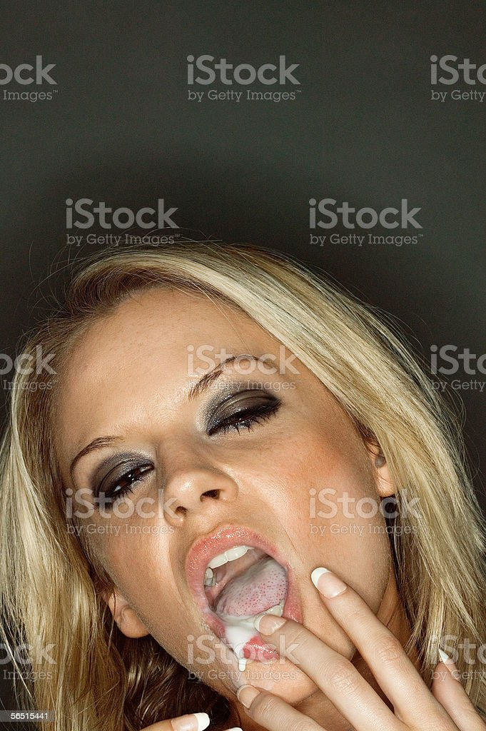 Cream dripping from woman's mouth stock photo
