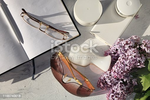 Cream for skin care, deodorant on a sunny table, a notebook for work and glasses and colorful branches of lilac, preparation for summer rest in the sun, copy space, top view.