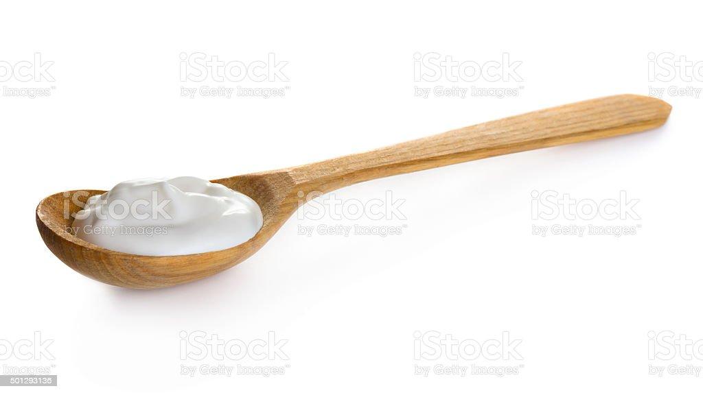 Cream in wooden spoon stock photo