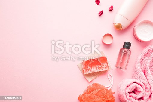 istock Cream jars, shower bottle, essential oil, towel, orange wisp and soap on pastel pink table. Relax products for body washing. Empty place for text, quote, sayings or logo. 1135696904