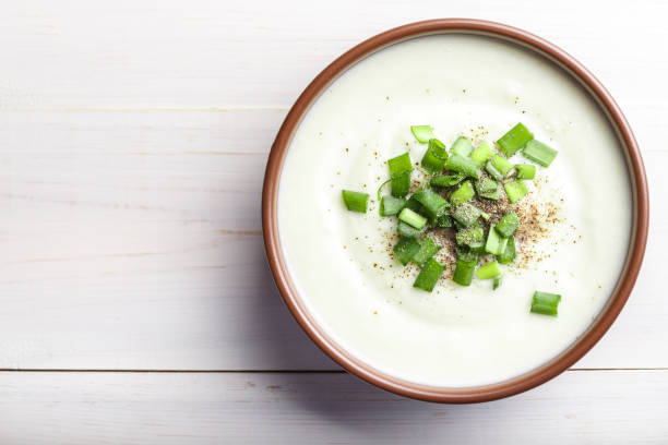 cream of cauliflower soup in a clay plate on a white wooden background. the soup is decorated with finely chopped green onions stock photo
