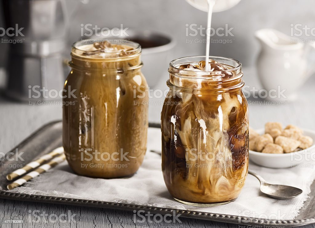 Cream or Milk Pouring Into Iced Coffee stock photo