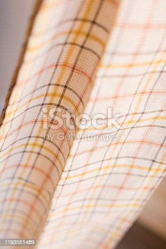 Cream, Orange & Yellow Plaid Material. Taken in bright natural light on a wooden floor.