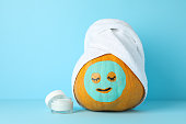 istock Cream, pumpkin with facial mask and towel on blue background, copy space 1178963658