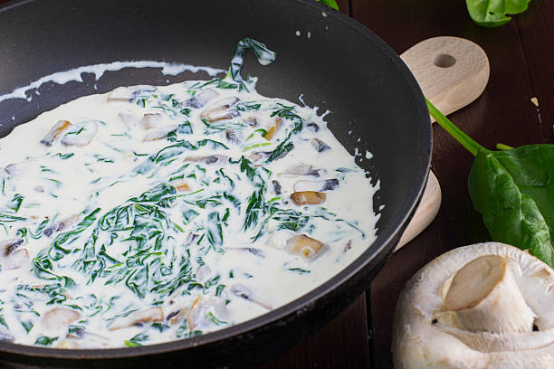 cream sauce with spinach and champignon mushrooms on the pan - huhn spinat pasta stock-fotos und bilder