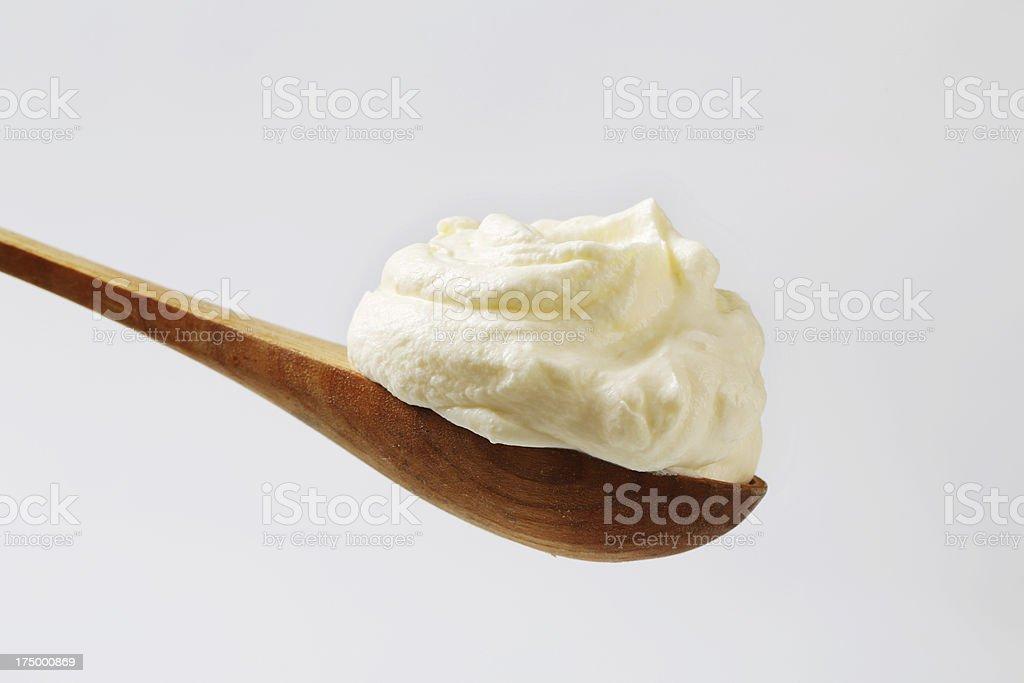 Cream spread on a wooden spoon stock photo