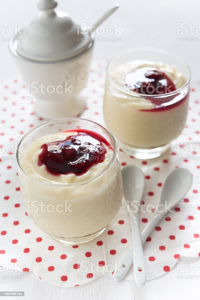 Creamy and fluffy semolina pudding with cherry sauce stock photo