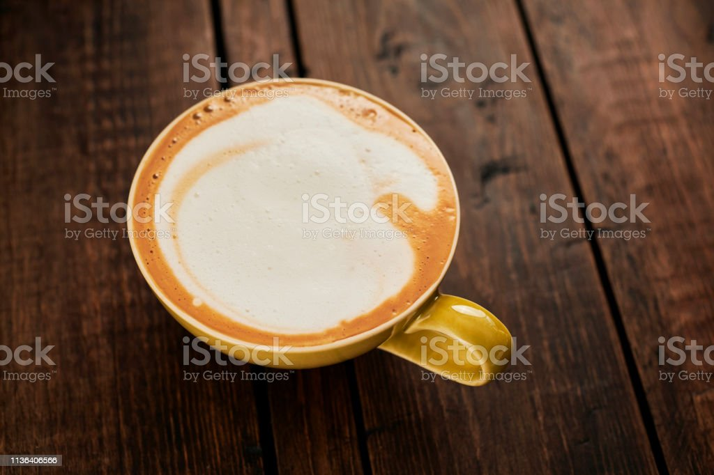 creamy Cappuccino Coffee on an aged wood table top stock photo