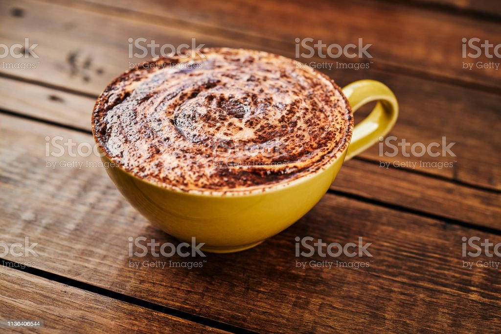 Creamy Cappuccino topped with chocolate swirled foam on a dark aged rustic wood table top. stock photo