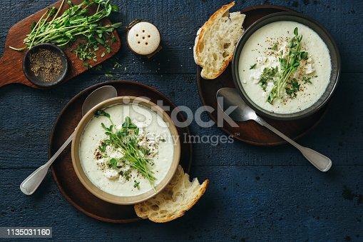 Creamy caulflower and broccoli with feta soup on dark blue background