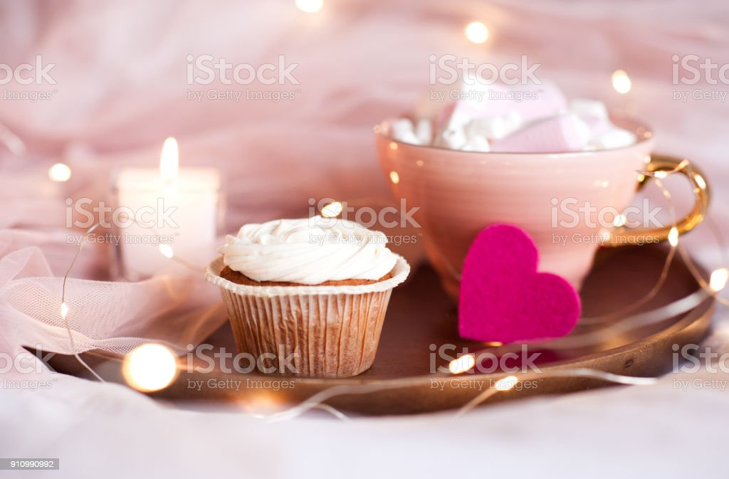 Cupcake with cup of coffee on tray in bed close up over lights....