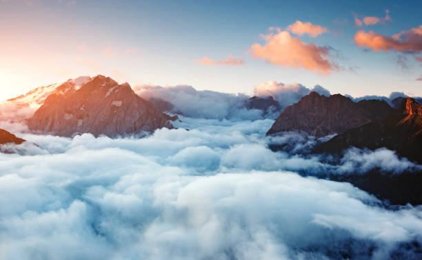 Creamy fog covered the famous glacier Marmolada. Location place Val di Fassa valley, passo Sella, Dolomiti, South Tyrol. Italy, Europe.