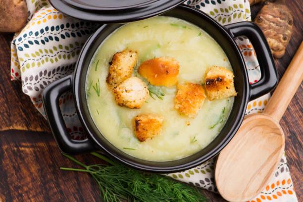 Creamy Jerusalem artichoke soup on wooden background stock photo