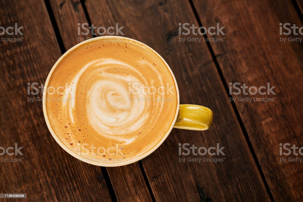 creamy Latte coffee with a swirl pattern on an aged dark wood table top. stock photo