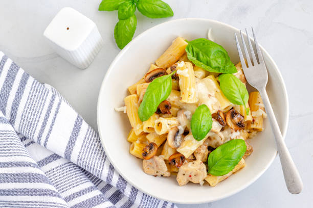 Creamy Mushroom and Chicken Pasta Garnished with Fresh Basil Leaves Creamy Mushroom and Chicken Pasta Garnished with Fresh Basil Leaves Top View, Cooked Rigatoni Pasta Photography. rigatoni stock pictures, royalty-free photos & images