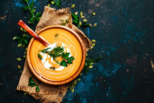 Creamy pumpkin soup in a wooden bowl