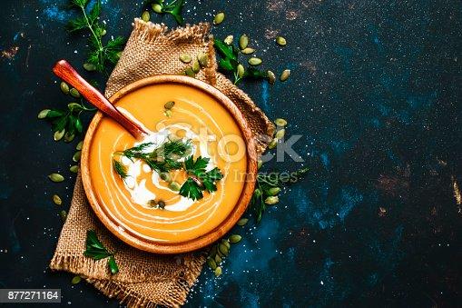 istock Creamy pumpkin soup in a wooden bowl 877271164