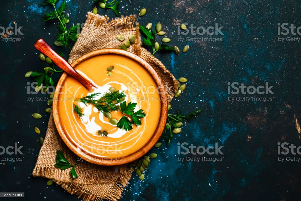 Creamy pumpkin soup in a wooden bowl stock photo