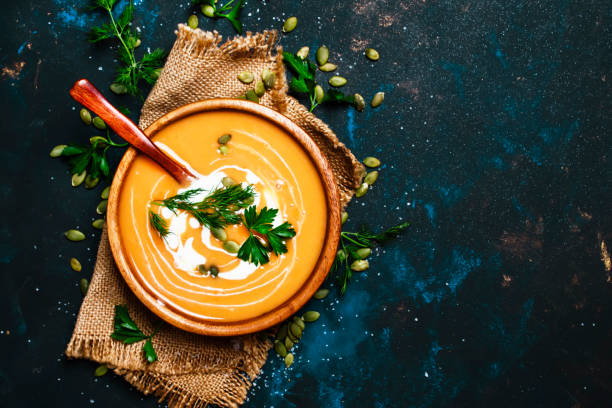 Creamy pumpkin soup in a wooden bowl Creamy pumpkin soup in a wooden bowl, blue background, top view squash vegetable stock pictures, royalty-free photos & images