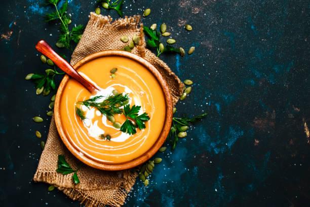 creamy pumpkin soup in a wooden bowl - sopa imagens e fotografias de stock
