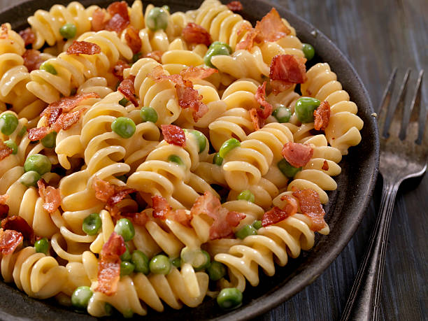 Creamy Rotini and Cheese Carbonara with Peas Creamy Rotini and Cheese Carbonara with Peas -Photographed on Hasselblad H3D2-39mb Camera fusilli stock pictures, royalty-free photos & images