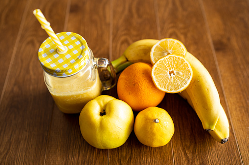 Creamy smoothie from orange, lemon, banana and quince in glass cups with paper tubes on a light background. no plastic. healthy food, vitamins