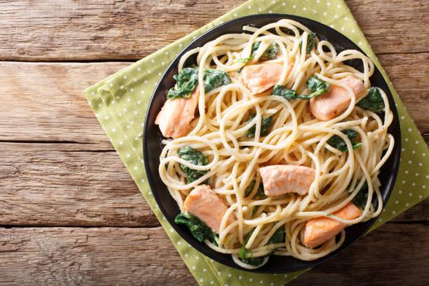 cremige spaghetti mit lachs und spinat nahaufnahme auf einer platte. horizontale ansicht von oben - spaghetti mit spinat stock-fotos und bilder