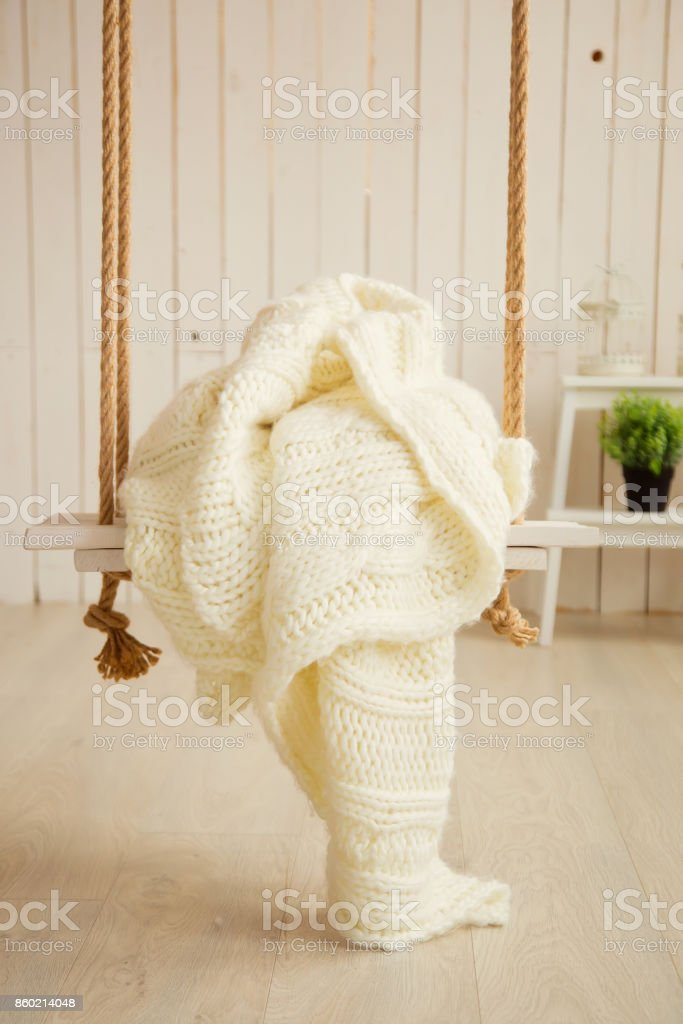 Creamy sweater on wooden swing with rope stock photo