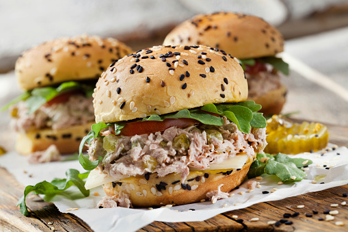 Creamy Tuna Salad Sliders with Sweet Pickles, Swiss Cheese, Tomato and Arugula on Brioche Sesame Seed Buns