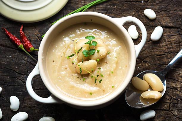 crema di zuppa di fagioli bianchi su sfondo in legno - fagioli cannellini foto e immagini stock