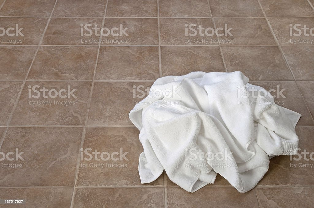 Creased white towels on ceramic floor stock photo
