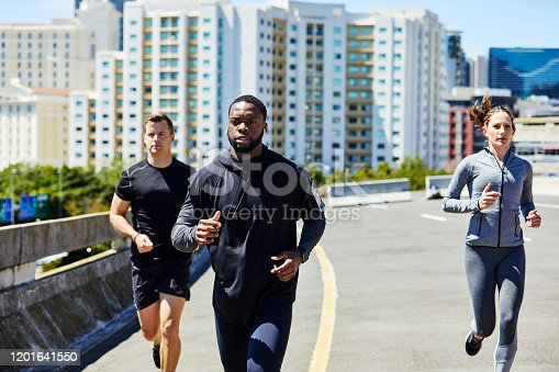Shot of a group of sporty young people out for a run in the city