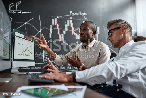 Two diverse colleagues traders talking to each other, looking at graphs while sitting in the office in front of multiple computer screens. Stock trading, people, business concept.