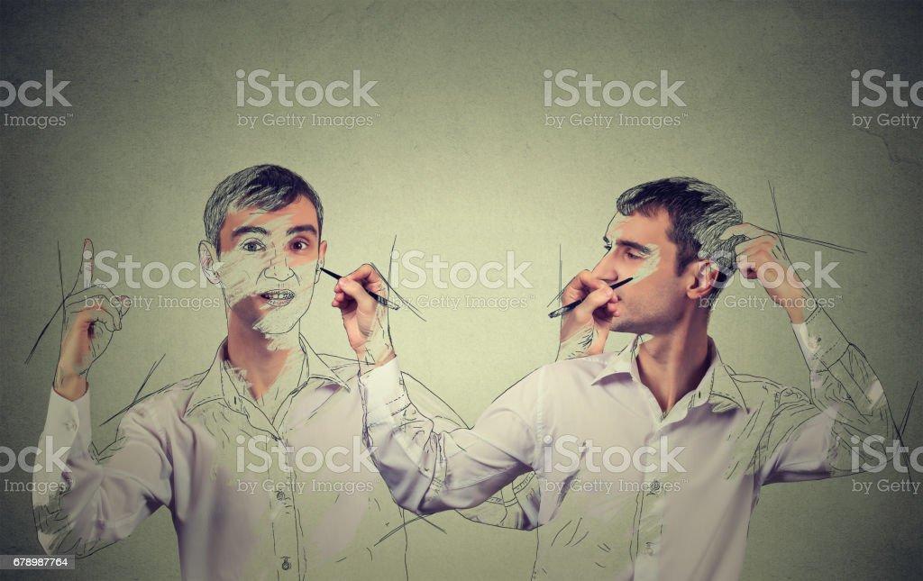 Kendini kavram oluşturun. Genç adam bir resim çizim yakışıklı, kendini gri duvar arka plan üzerinde kroki royalty-free stock photo