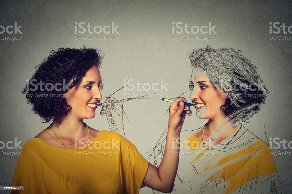 Create yourself, your image concept. Attractive young woman drawing a picture, sketch of herself stock photo