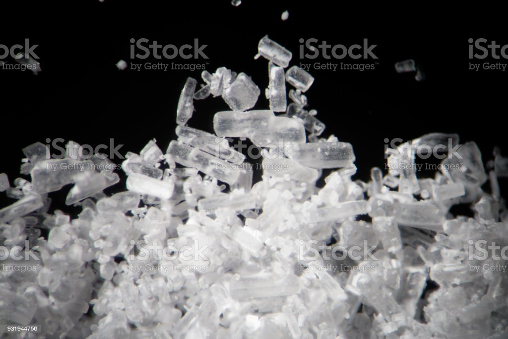 Creatine crystals by microscope. Athletic dietary supplement in details supermacro close-up. White cristales on black background or low key stock photo